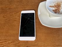 Mobile cracked tuchscreens for communications is brocken placed on a wooden table and coffee mugs in coffee shop. Mobile seriously cracked tuchscreens for royalty free stock images