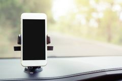 Mobile smart phone with black screen in car console holder stick front. insert map gps navigation on the in the background. Of the dashboard. empty screen for stock image