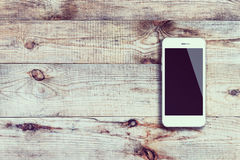 Mobile smart phone with black screen on wooden background. Royalty Free Stock Image