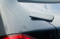 Mobile smart phone on car boot background Stock Photo