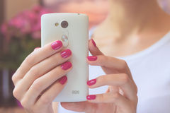 Mobile smart phone in female hands with a pink manicure on the b. Ackground of pink flower and girl in a white T-shirt. Soft light Royalty Free Stock Photo