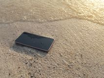 Mobile smart phone on the sandy beach with soft waves of sea background. Internet of things concept.  royalty free stock photography