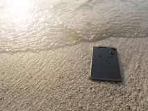 Mobile smart phone on the sandy beach with soft waves of sea background. Internet of things concept. Mobile smart phone on the sandy beach with soft waves of royalty free stock photos