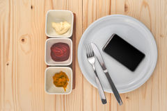 Mobile smart phone served as dinner on white plate. Concept of information absorption process royalty free stock photography
