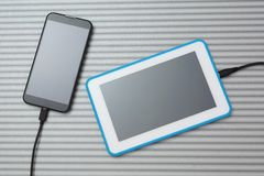 Mobile smart phone and tablet pc charging on silver desk Royalty Free Stock Photos