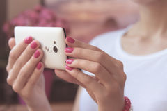 Mobile smart phone in women's hands with a pink manicure on the. Background of pink flower and girl in a white T-shirt. Soft light Stock Photography
