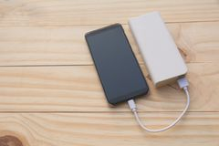 Mobile smart phones charging with power bank on desk and copy sp. Ace Royalty Free Stock Photos