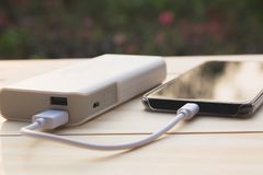 Mobile smart phones charging with power bank on desk and copy sp. Ace Royalty Free Stock Photo