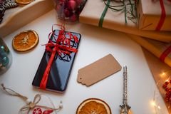 Mobile smartphone tied with a red ribbon surrounded by gifts and other Christmas trifles royalty free stock photography
