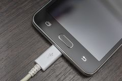 Mobile smart phones charging on wooden desk. Mobile smartphones charging a white wire on a wooden table Royalty Free Stock Images