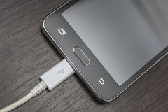 Mobile smart phones charging on wooden desk. Mobile smartphones charging a white wire on a wooden table Stock Images