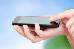 Mobile smatphone in woman's hands Stock Image