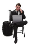Mobile technology. Young and tired traveler businessman working on a laptop while is calling by phone next to his suitcase Stock Photos