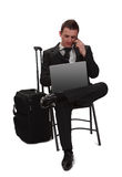 Mobile technology. Young and tired traveler businessman working on a laptop while is calling by phone next to his suitcase Stock Images