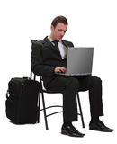 Mobile technology. Young traveler businessman working on a laptop next to his suitcase Royalty Free Stock Photography