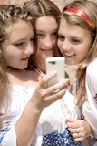 Mobile Teen Fun. Three Teenagers looking at the white Mobile Phone close up Stock Images