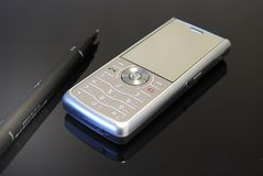 Mobile telephone. Silver mobile phone and pen in black background Stock Images