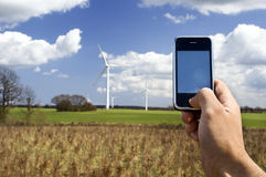 Mobile telephone and wind farm Stock Images