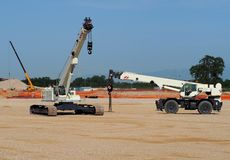 Mobile telescopic cranes with tracks and wheels in a construction site. Mobile telescopic cranes with tracks and wheels in a just opened construction site stock photography