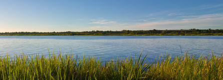 River with Grass in the Foreground and Blue Sky Stock Photos