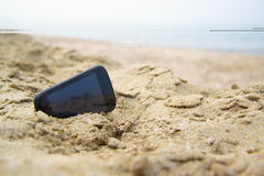 Mobile touch phone in sand on beach Royalty Free Stock Image