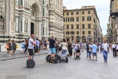 Mobile tour of Florence. FLORENCE, ITALY - SEPTEMBER 12, 2018: These are unidentified tourist on the segway in a mobile tour near the Cathedral of the city stock image