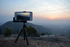 Mobile on tripod taking picture. A picture of a phone recording video of the sunset in a mountain region Royalty Free Stock Photography