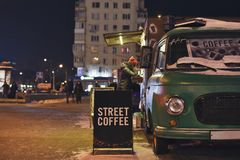 Mobile truck on wheels in the winter night. Buying coffee in a mobile truck on wheels in the winter night stock photos