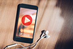 Mobile with viral video advertising on phone screen at blur wood. Table,share video on social media concept,Digital marketing strategy Royalty Free Stock Photo