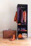 Mobile wardrobe with clothing and leather suitcase. Mobile wardrobe with orange and purple clothing, and leather suitcase stock photo
