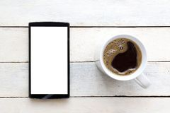 Mobile on a white wooden table next to coffee in a mug. Top view and empty copy space. For Editor`s text Royalty Free Stock Photo