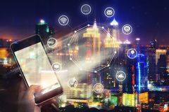 Mobile with wireless communication network and night city background. E-commerce business. internet of things. royalty free stock image