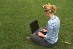 Mobile working. Woman sitting on grass and working with laptop computer Stock Photo