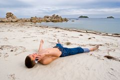Mobile and the young man. The young man talks on mobile on a deserted beach Royalty Free Stock Images