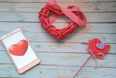 Smart heart beats. Smartphone with red hearts and red bird on a wooden blue background. St Valentine`s theme. Mobilephone with a red heart. Red heart and a red Royalty Free Stock Images