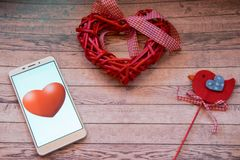 Smart heart beats. Smartphone with red hearts and red bird on a wooden blue background. St Valentine`s theme. Mobilephone with a red heart. Red heart and a red Stock Photography