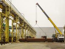 Mobiler Kran entlädt Stahlrohre Stockfotos