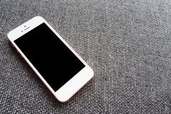 Mobiler leerer Bildschirm des nahen hohen Telefons auf Draufsicht des Sofas, Modell lizenzfreies stockfoto