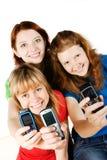 Mobiles della holding dei giovani immagine stock
