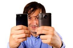 Mobiles della holding dell'uomo d'affari fotografia stock libera da diritti