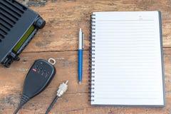 Mobilfunktransceiver und -notizbuch auf hölzerner Tabelle Stockbild