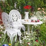Mobili da giardino messi con la crescita di fiori nel giardino Fotografia Stock Libera da Diritti