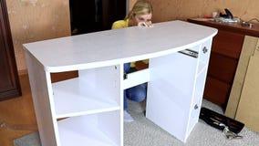 Mobilia bianca del montaggio della donna nuova, lei che mette un ripiano del tavolo su una tavola di condimento montata nuova met archivi video