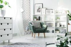 Mobilia bianca e poltrona verde fotografia stock