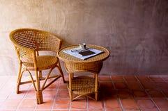 Mobilia del rattan con il caffè del libro ed i vetri sopra la tavola, d Immagini Stock