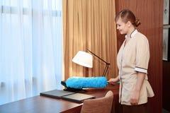 Mobilia della spolverata della domestica dell'hotel fotografia stock libera da diritti