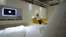 Mobilia di acquisto della donna nel salone moderno del plasma TV della sedia di prova del deposito di IKEA, stock footage