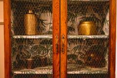 Mobilia di legno antica con gli oggetti bronzei dentro fotografia stock libera da diritti
