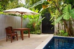 Mobilia di legno coperta dall'ombrello in giardino Fotografia Stock