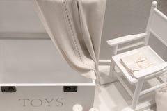 Mobilia di legno naturale bianca nella stanza dei bambini sotto forma di cassetto e di sedia di oscillazione fotografia stock